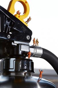 消化器の上で働くミニチュア消防士の写真素材 [FYI01461504]