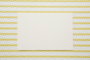 黄色と白のストライプの上に置かれた紙の写真素材 [FYI01461506]
