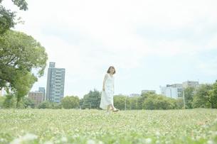 草原の中歩く若い女性の写真素材 [FYI01461521]