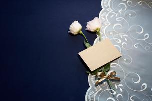 紺色テーブルクロスの上に置かれたレースとピンクの花とメッセージカードの写真素材 [FYI01461599]