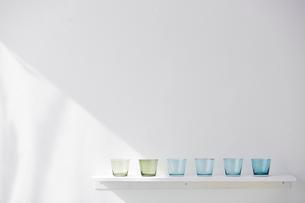 白い棚の上に並べられたブルーとグリーンのガラスのコップの写真素材 [FYI01461615]