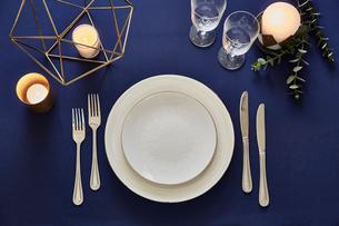 紺色のテーブルクロスの上でセッティングされた皿とカトラリーの写真素材 [FYI01461640]