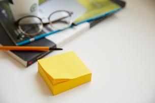 テーブルの上のコーヒーと付箋とメガネの写真素材 [FYI01461650]