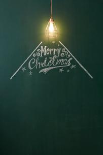光るペンダントライトと黒板に描かれたメリークリスマスの文字の写真素材 [FYI01461671]