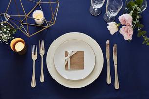 紺色のテーブルクロスの上でセッティングされた皿とカトラリーの写真素材 [FYI01461688]