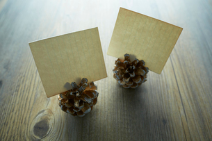 テーブルの上に置かれた紙が刺さったマツボックリの写真素材 [FYI01461776]