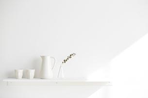 白い棚の上に並べられた白いコップとポットと花器の写真素材 [FYI01461786]