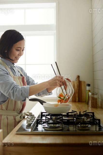 キッチンで調理をする女性の写真素材 [FYI01461792]