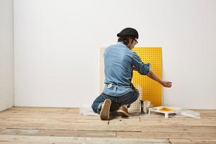 有孔パネルを塗る男性の写真素材 [FYI01461793]