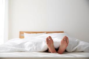 明るい光の入ったシンプルなベッドルームと眠る男性の写真素材 [FYI01461820]