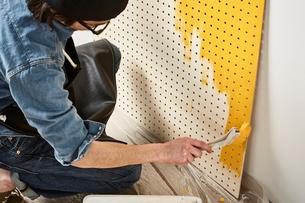 有孔パネルを塗る男性の写真素材 [FYI01461867]