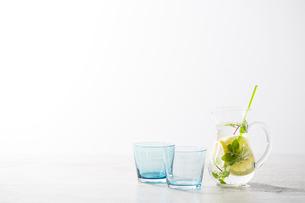 二つのガラスのコップとレモンとミントと炭酸水の入ったガラスピッチャーの写真素材 [FYI01461916]
