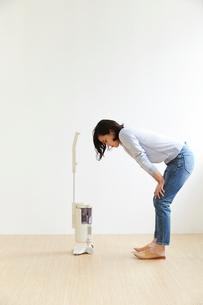 掃除機の横で床を見つめる女性の写真素材 [FYI01461919]