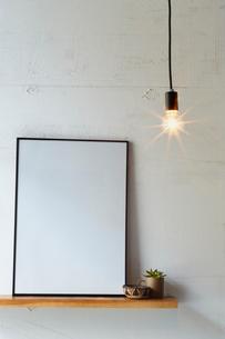 ペンダントライトと棚に置かれた白い額の写真素材 [FYI01461922]