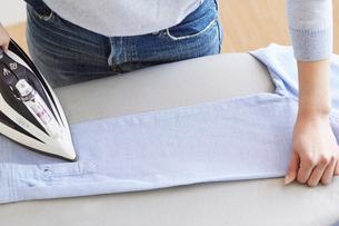 シャツのアイロンがけをする女性の手元の写真素材 [FYI01461951]