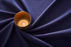 紺色のテーブルクロスの上に置かれたキャンドルの写真素材 [FYI01461974]