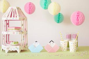 テーブルの上に置かれた折り紙で作られた雛人形とパーティーグッズの写真素材 [FYI01461987]