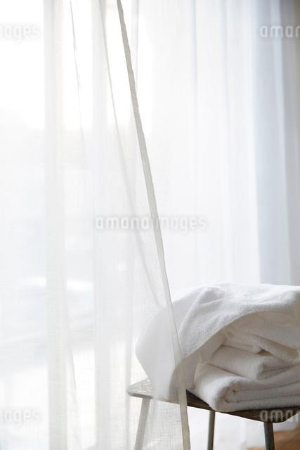 明るい窓際に置かれたタオルとスツールの写真素材 [FYI01462016]