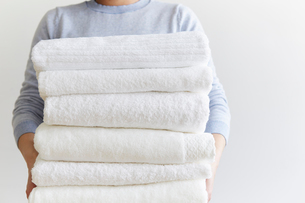 重ねたタオルを抱える女性の写真素材 [FYI01462023]