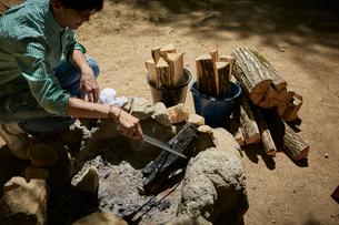 薪をつつく一人の男性の写真素材 [FYI01462043]