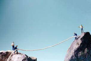 2つの岩山の上でロープを引き合う男性の写真素材 [FYI01462062]