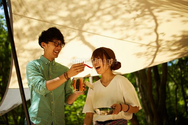キャンプでピクルスを食べながら作業するカップルの写真素材 [FYI01462066]