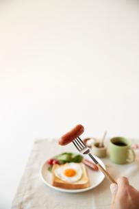 白い背景の朝食イメージとウインナーを食べようとしている人の手の写真素材 [FYI01462082]