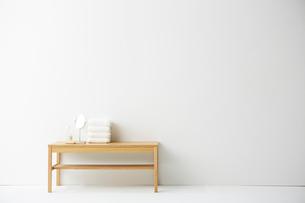 ナチュラルカラーのベンチの上に置かれたタオルとミラーの写真素材 [FYI01462091]