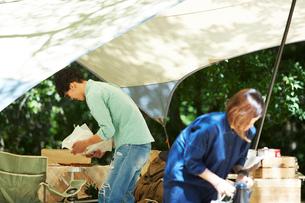タープの下で料理の準備をする男女の写真素材 [FYI01462107]