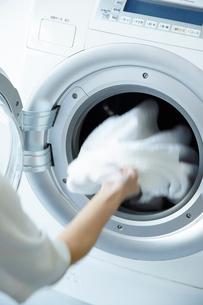 ドラム式洗濯機に洗濯物を入れる女性の手の写真素材 [FYI01462131]