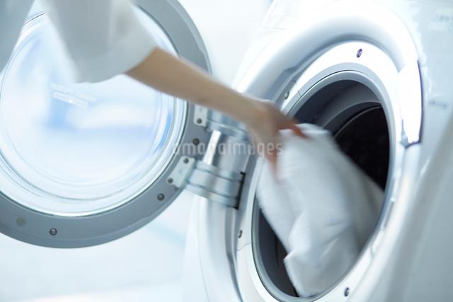 ドラム式洗濯機に洗濯物を入れる女性の手の写真素材 [FYI01462138]