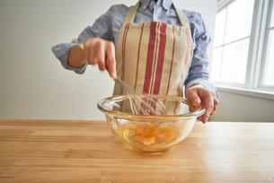 キッチンで卵を溶く女性の写真素材 [FYI01462139]
