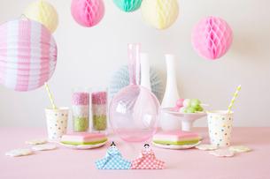 テーブルの上に置かれた折り紙で作られた雛人形とパーティーグッズの写真素材 [FYI01462142]