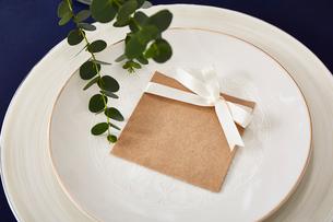 紺色のテーブルクロスの上でセッティングされた皿とメッセージカードの写真素材 [FYI01462168]