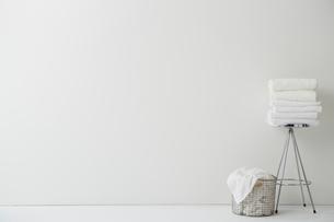 白い空間に置かれた畳まれたタオルと洗濯物の写真素材 [FYI01462171]