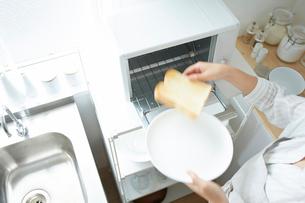 トースターでパンを焼く女性の写真素材 [FYI01462172]