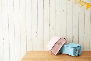 ガーランドが飾ってある板壁の前に置かれたピンクと水色のランドセルの写真素材 [FYI01462204]