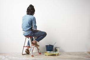 壁を向いて脚立に座っている男性の写真素材 [FYI01462220]