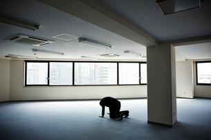 何もないオフィスで両手両膝をつき落ち込む男性の写真素材 [FYI01462227]