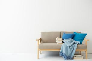 ソファの上にあるブルーのクッションとブランケットの写真素材 [FYI01462229]