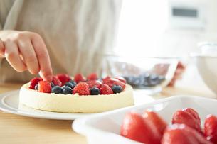 ケーキにフルーツをデコレーションする女性の手元の写真素材 [FYI01462232]