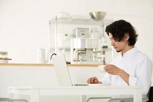 パソコンをしながらコーヒーを飲む男性の写真素材 [FYI01462236]