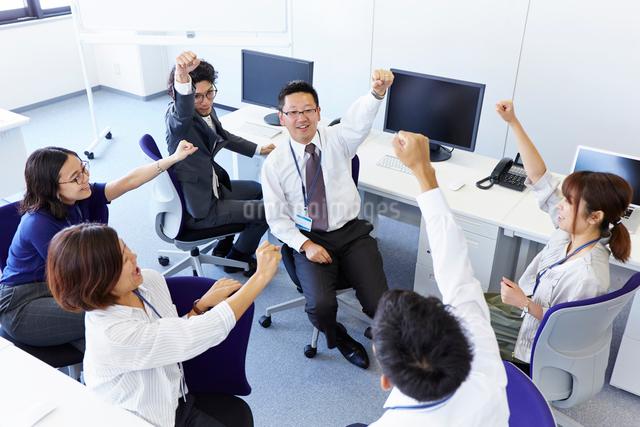 1人の男性を囲んで拳を上げている会社の仲間の写真素材 [FYI01462242]