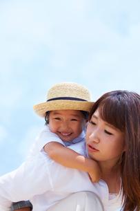 青空を背景に母親の背中に乗る子の写真素材 [FYI01462246]