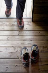 山小屋の入り口付近の床に置かれたトレッキングシューズと小屋に入る人の写真素材 [FYI01462247]