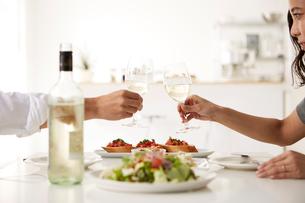 白いダイニングテーブルで食事する男女の写真素材 [FYI01462252]