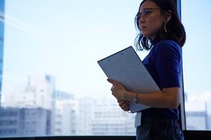 バインダーを持って窓際に立つ女性の写真素材 [FYI01462254]