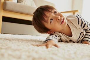 白いラグに寝転んでいる男の子の写真素材 [FYI01462269]