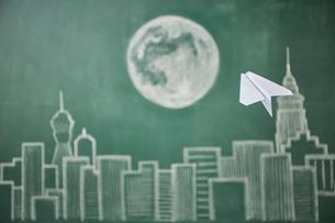 ビル群と満月が描かれた黒板イラストに飛ばした紙飛行機のイラスト素材 [FYI01462272]
