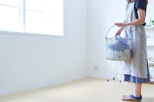 白い部屋で洗濯籠を持つ女性の写真素材 [FYI01462288]